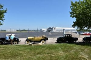 antique vehicles in front of TAT hanger at Port Columubs Airport